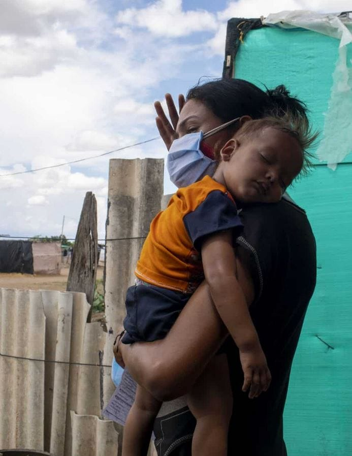 Mother and child outside of their shelter during a storm. Photo/Nicolo Filippo Rosso