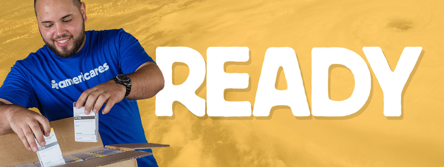 """image of an Americares worker with a box of supplies with the word, """"READY"""" in all caps"""
