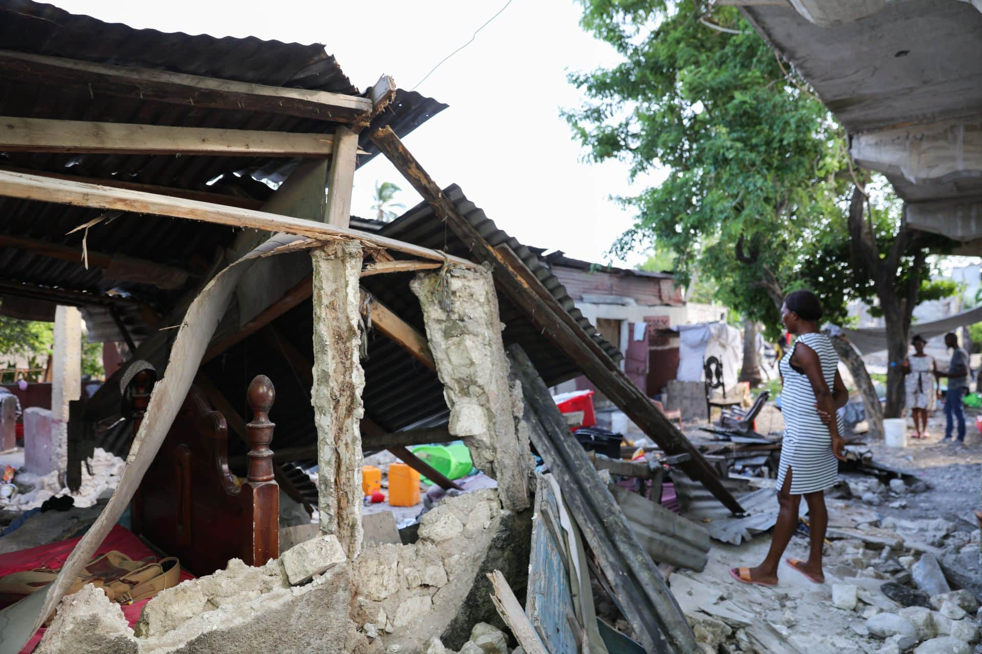 Woman stands in the earthquake wreckage
