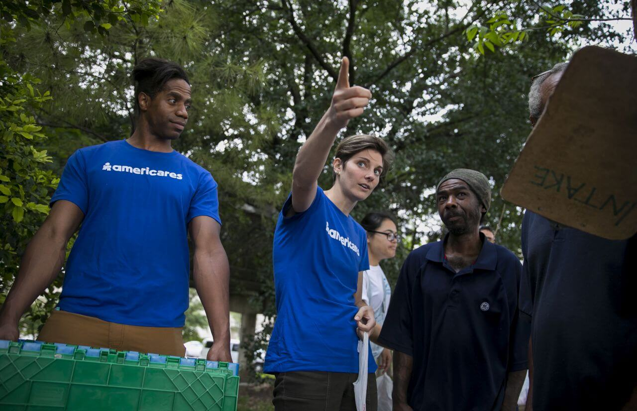An Americares worker points beyond the camera while others look in that direction.