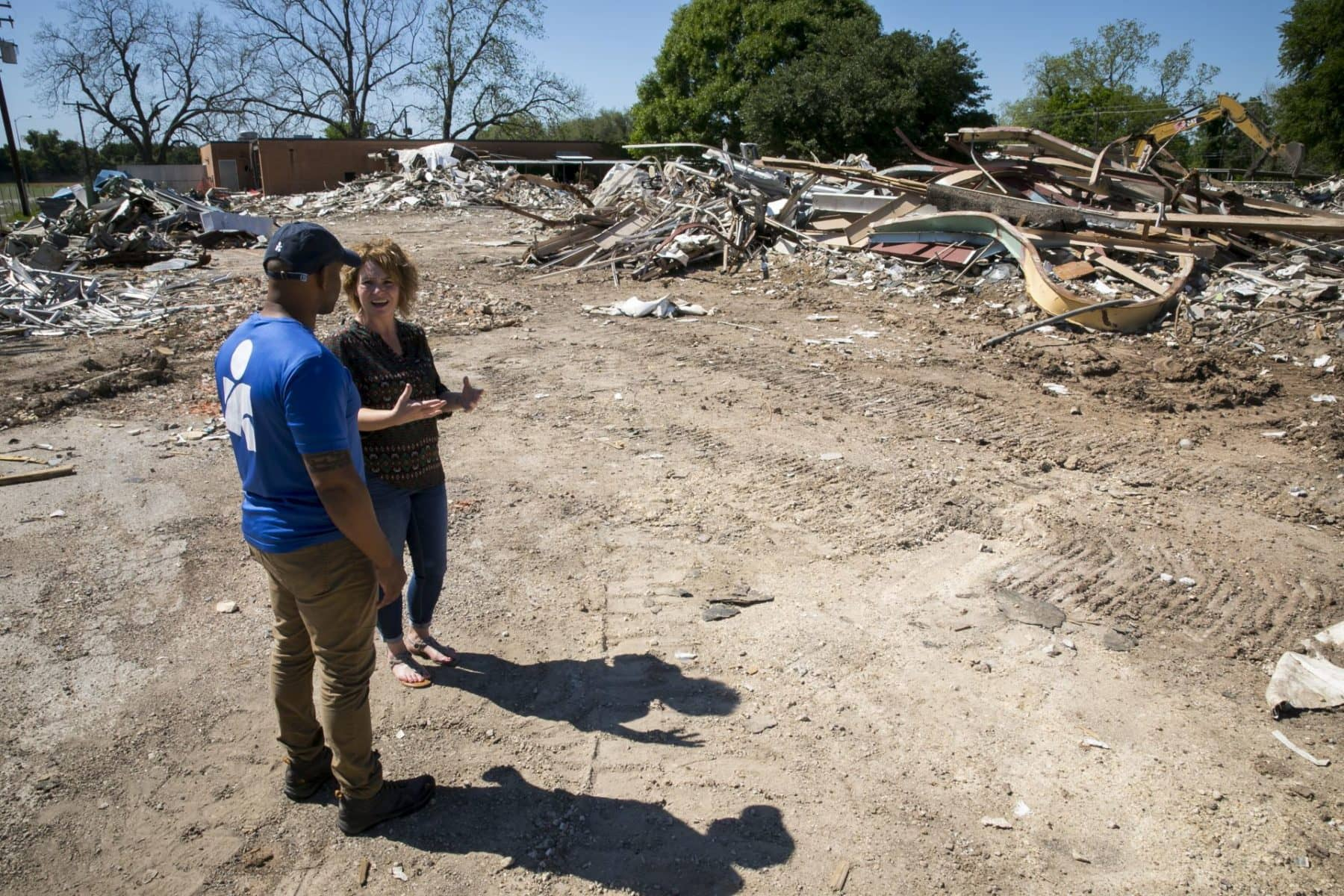 Stephanie Konvicka, who is organizing psychosocial programs for the Matagorda Episcopal Health Outreach Program to help Hurricane Harvey survivors cope with stress and trauma, gives Americares relief worker Curtis Barnes a tour of the storm recovery in her hometown of Wharton, Texas. Here they observe the demolition of the Just Do it Now community center, which was badly damaged in the storm. Konvicka is organizing yoga and art therapy classes to help community members come together and heal with funding from Americares Hurricane Harvey Recovery Program.