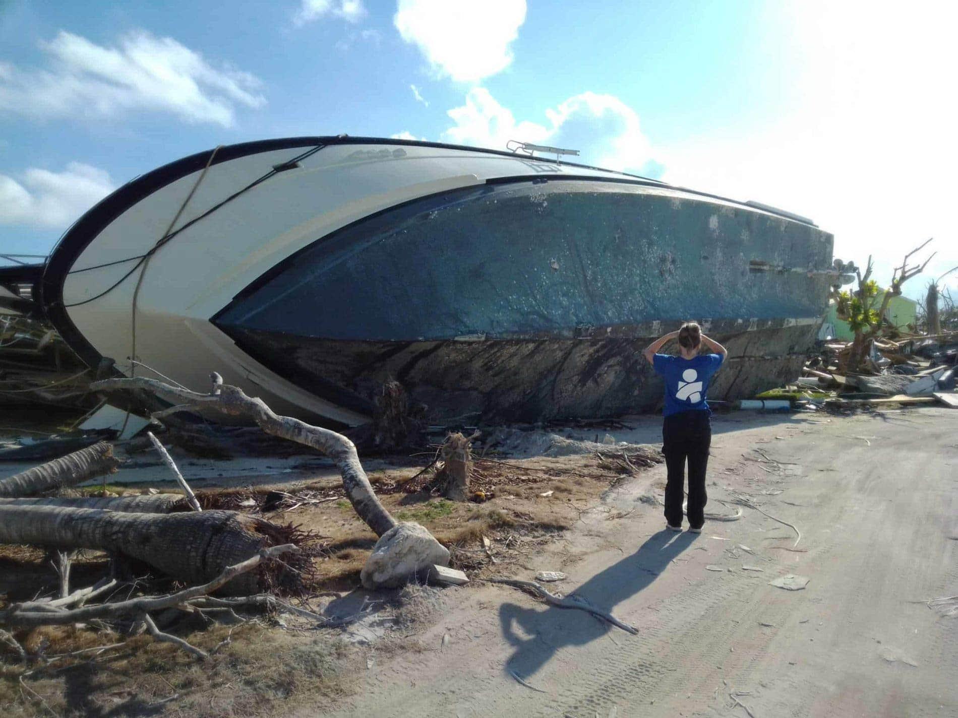 Bahamas Hopetown Americares worker looks at debris and boat damage