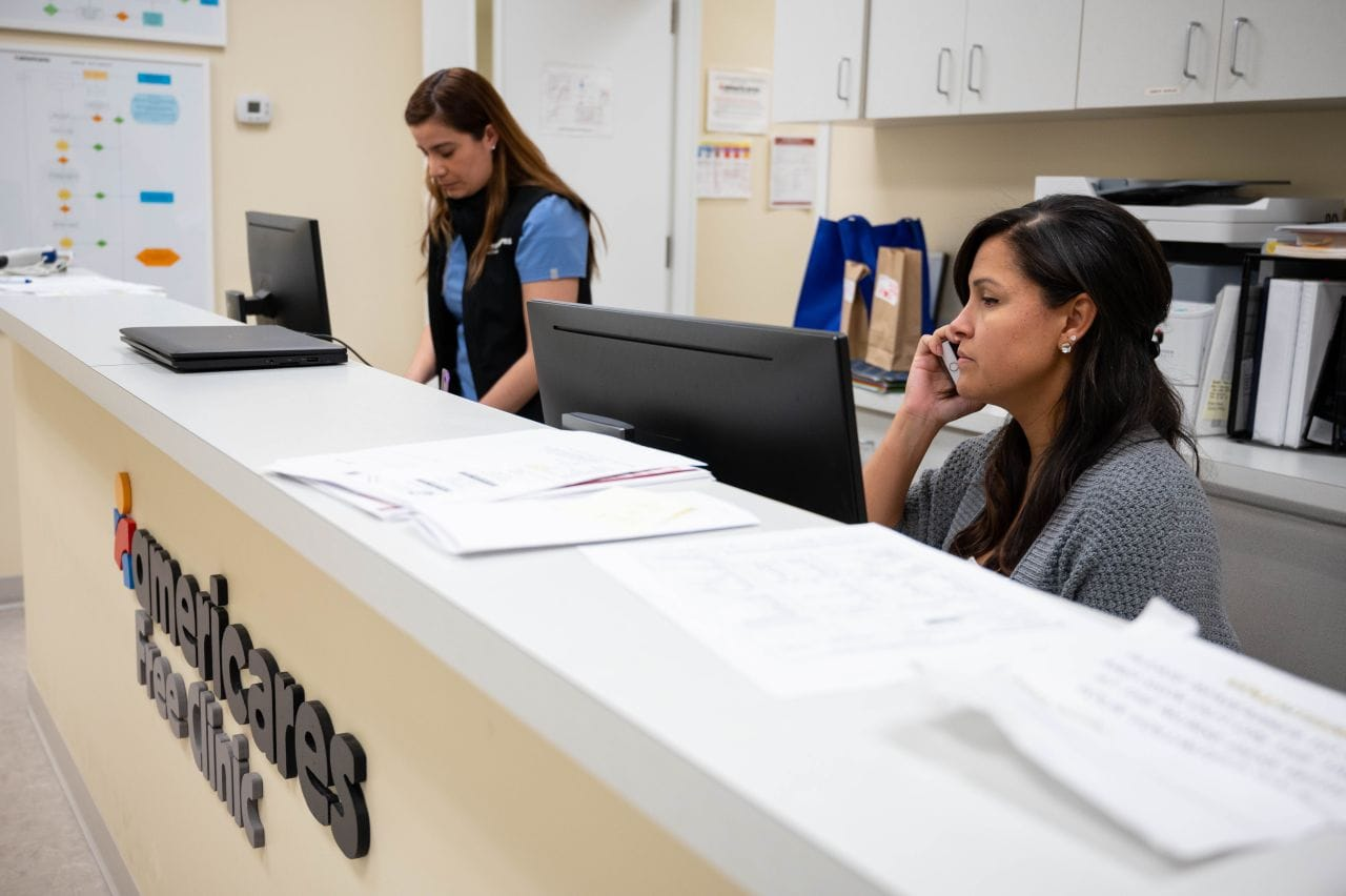 Two women at a reception desk with one holding a phone to her ear.