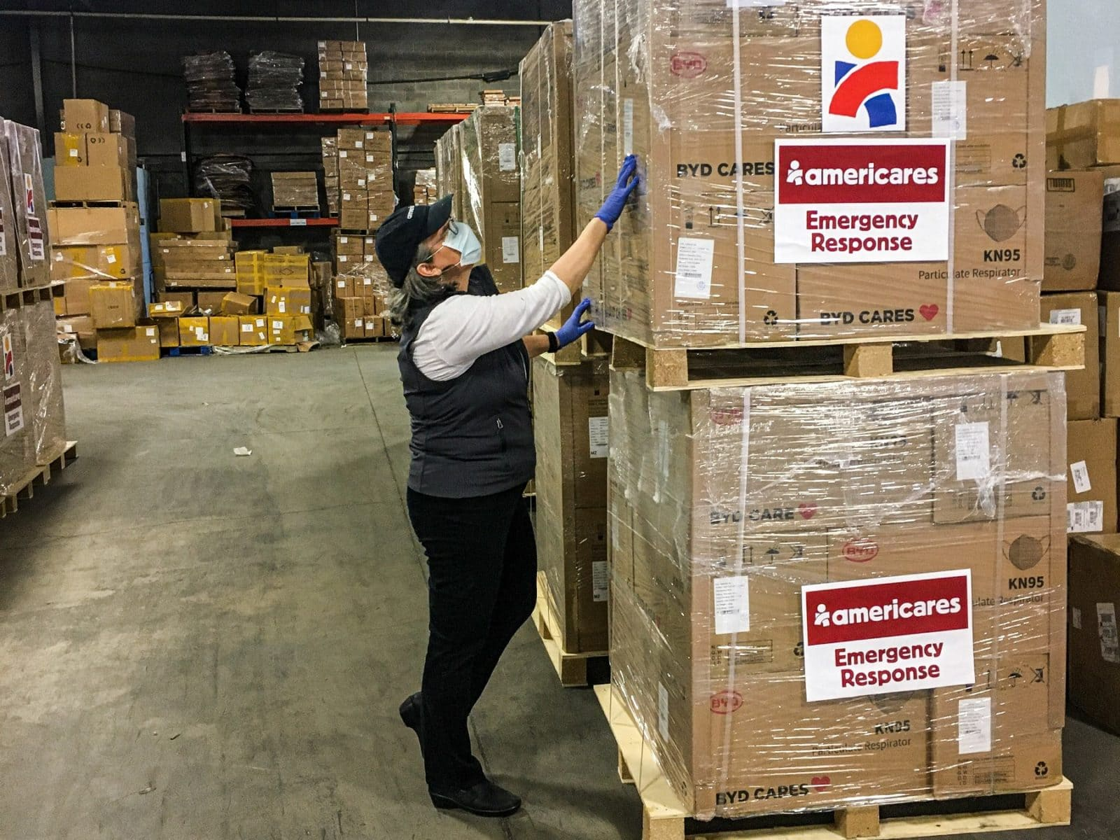 Americares Vice President of Global Program Operations Martha Kennard inspects a shipment of 300,000 KN95 masks for health workers in New York City. Photo courtesy of Americares.