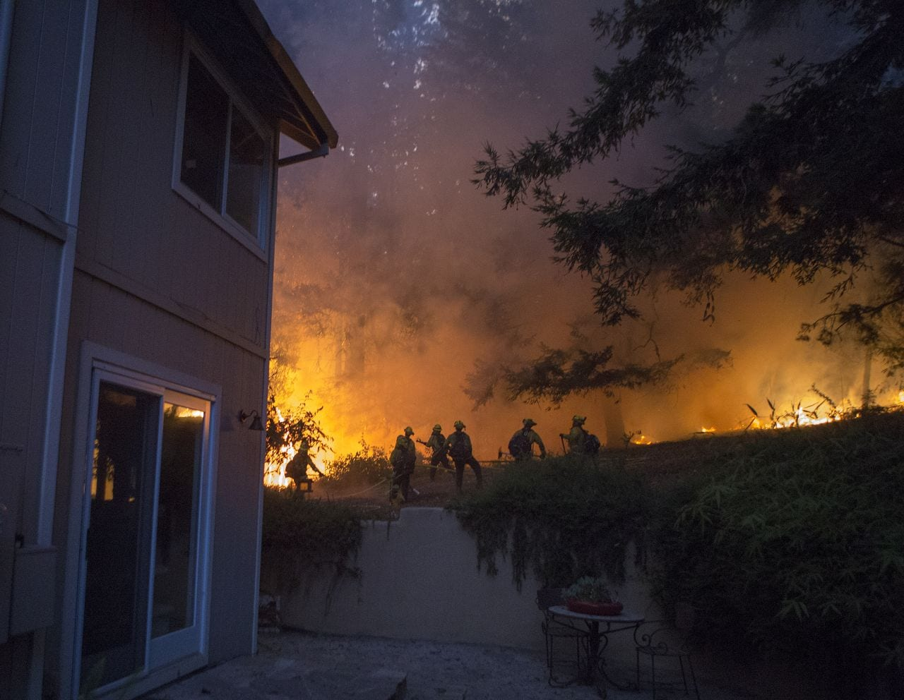 Fire outside of a home with firefighters combatting the blaze. Photo by David Royal