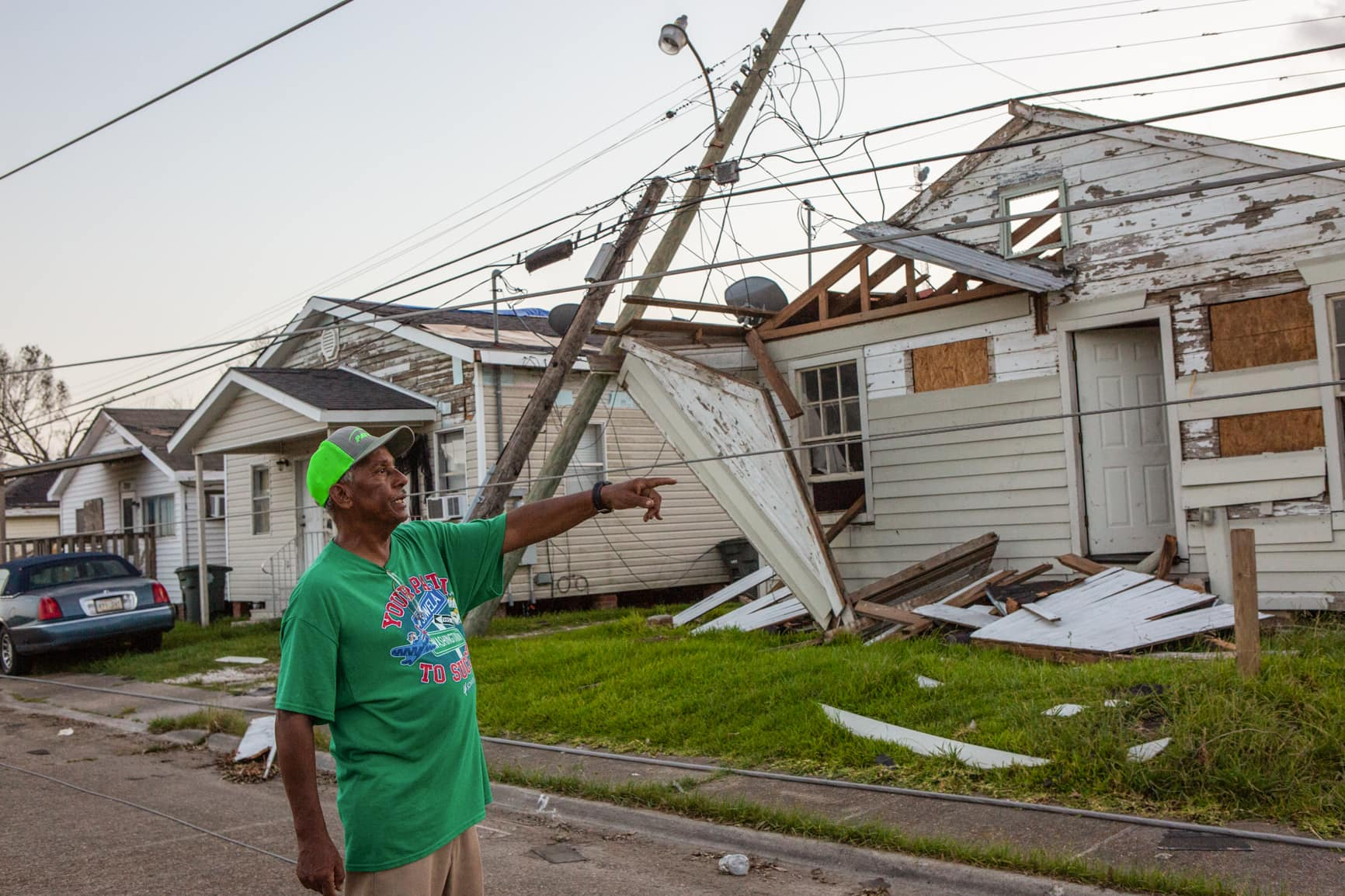 Michael H. Captain Sr. points to the damage created by Hurricane Laura on his street with damaged houses and a down telephone pole behind him.