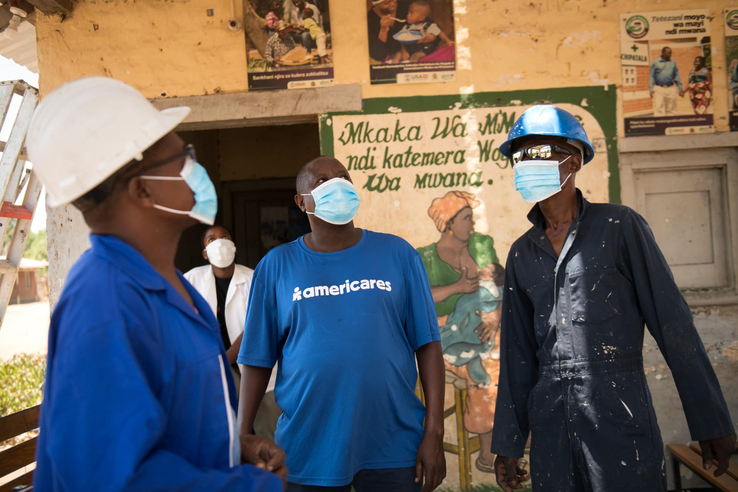 Akuzike Tasowana Americares Project Manager for Majete area interacts with construction workers at Chapananga Health Centre in southern Malawi where Americares have constructed a new secure water pump, water pump house, and painted the outpatient centre