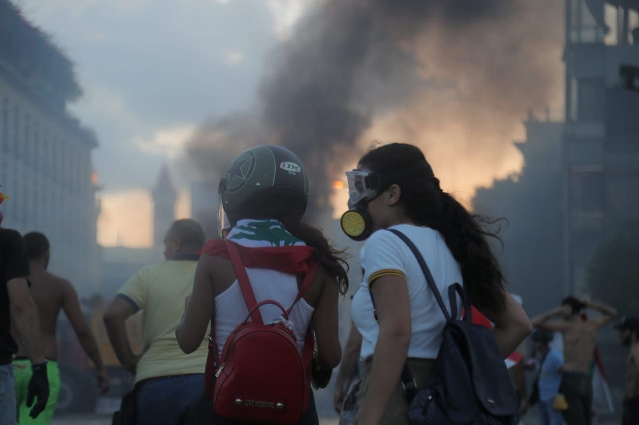 Two women in a small crowd protect themselves from smoke with a dust respirator and googles with a city building burning in the background.