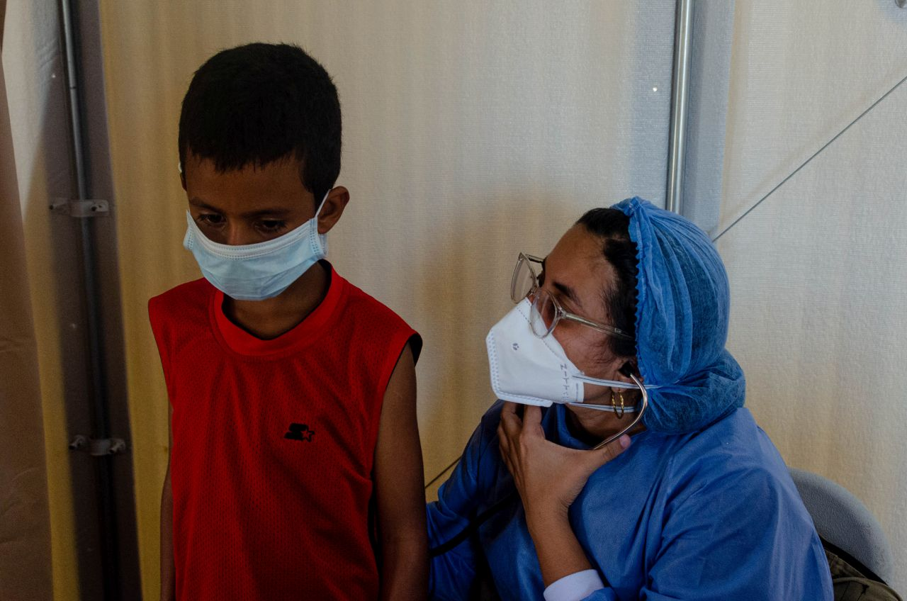 Lisbeth's son with a health care worker at Americares mobile clinic