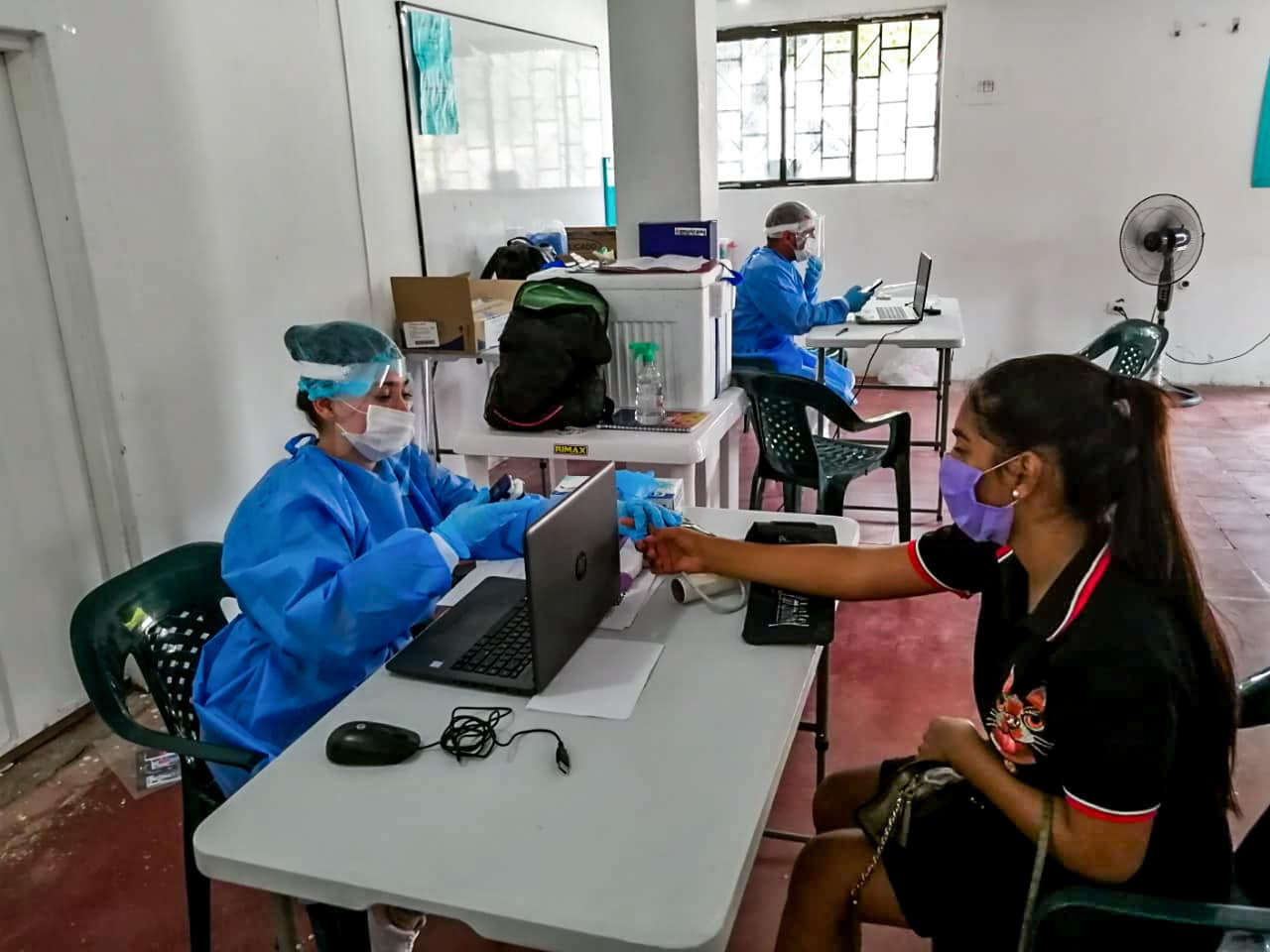 Head nurse interviewing patient sitting at a table in Colombia clinic