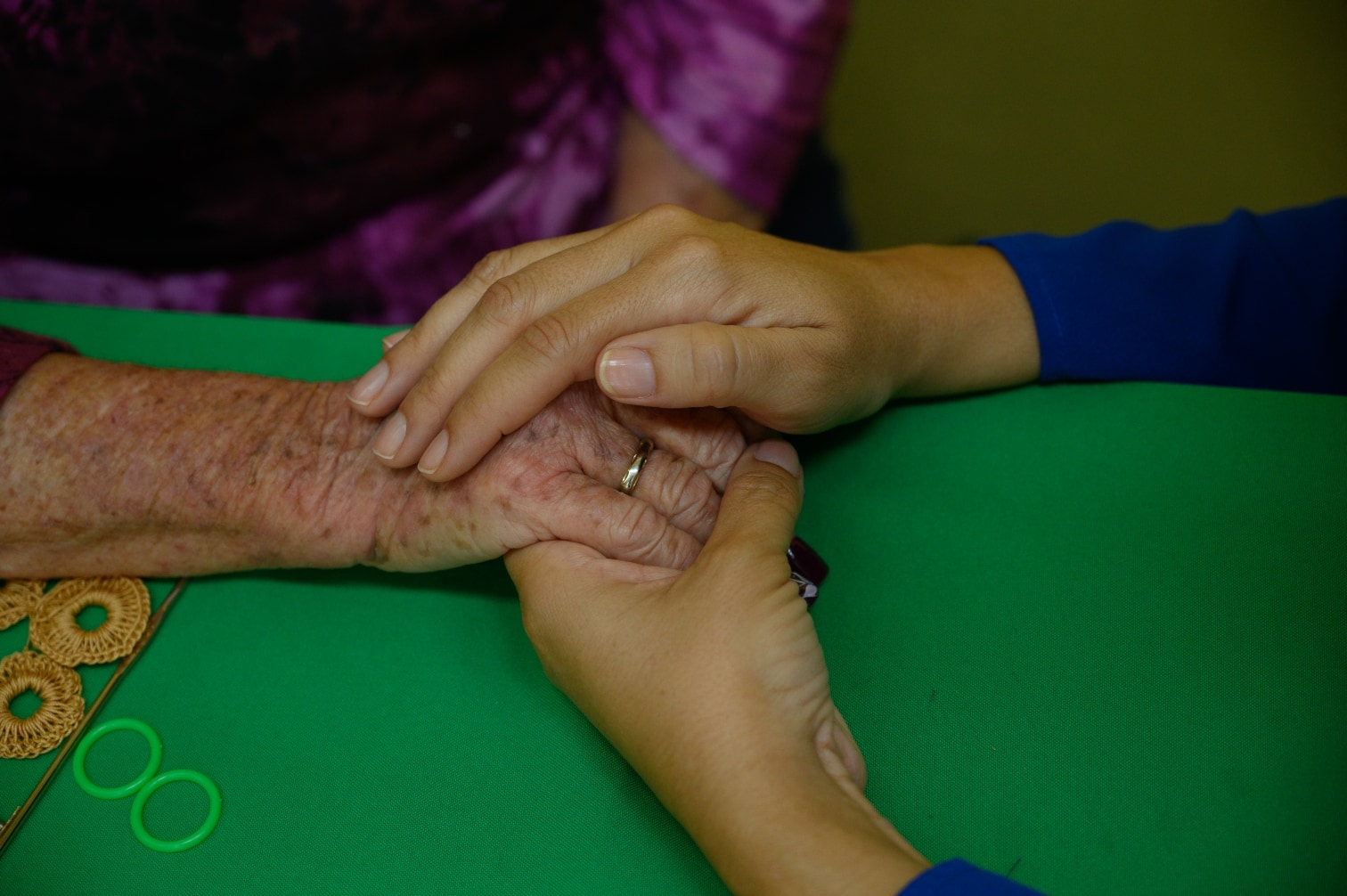 photo of an elderly person's hand being comforted by the hands of an Americares team member.