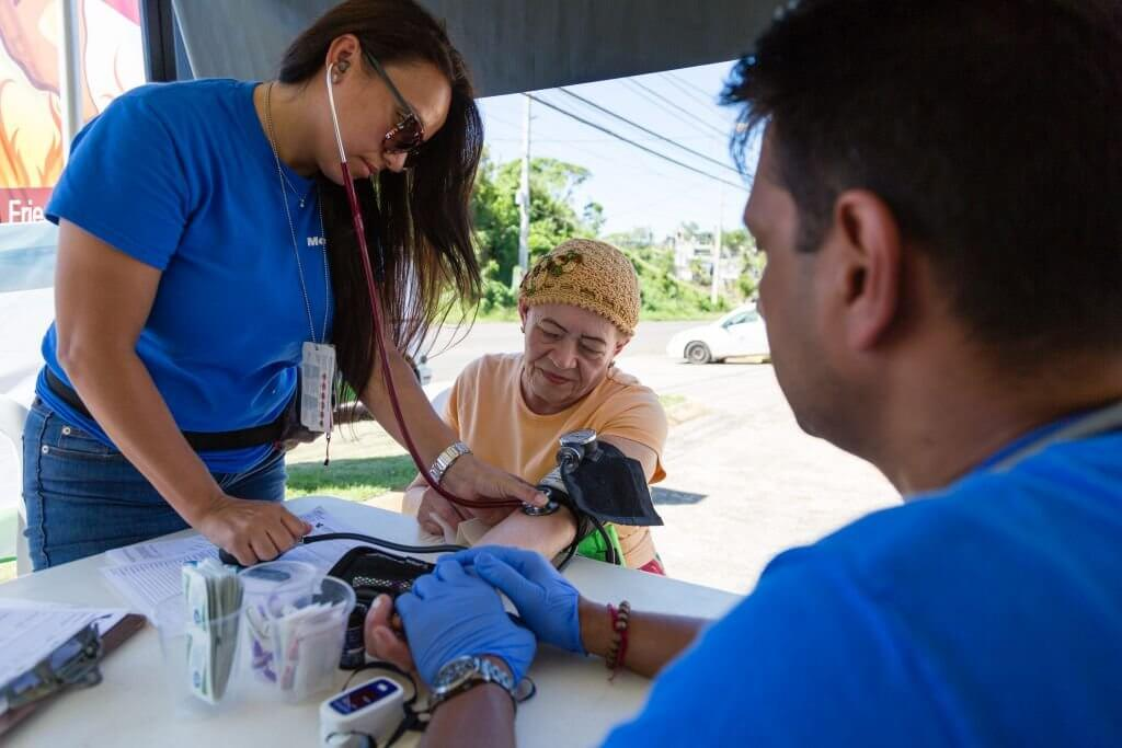 Two Americares medical staff take the blood pressure and heart rate of an older woman.