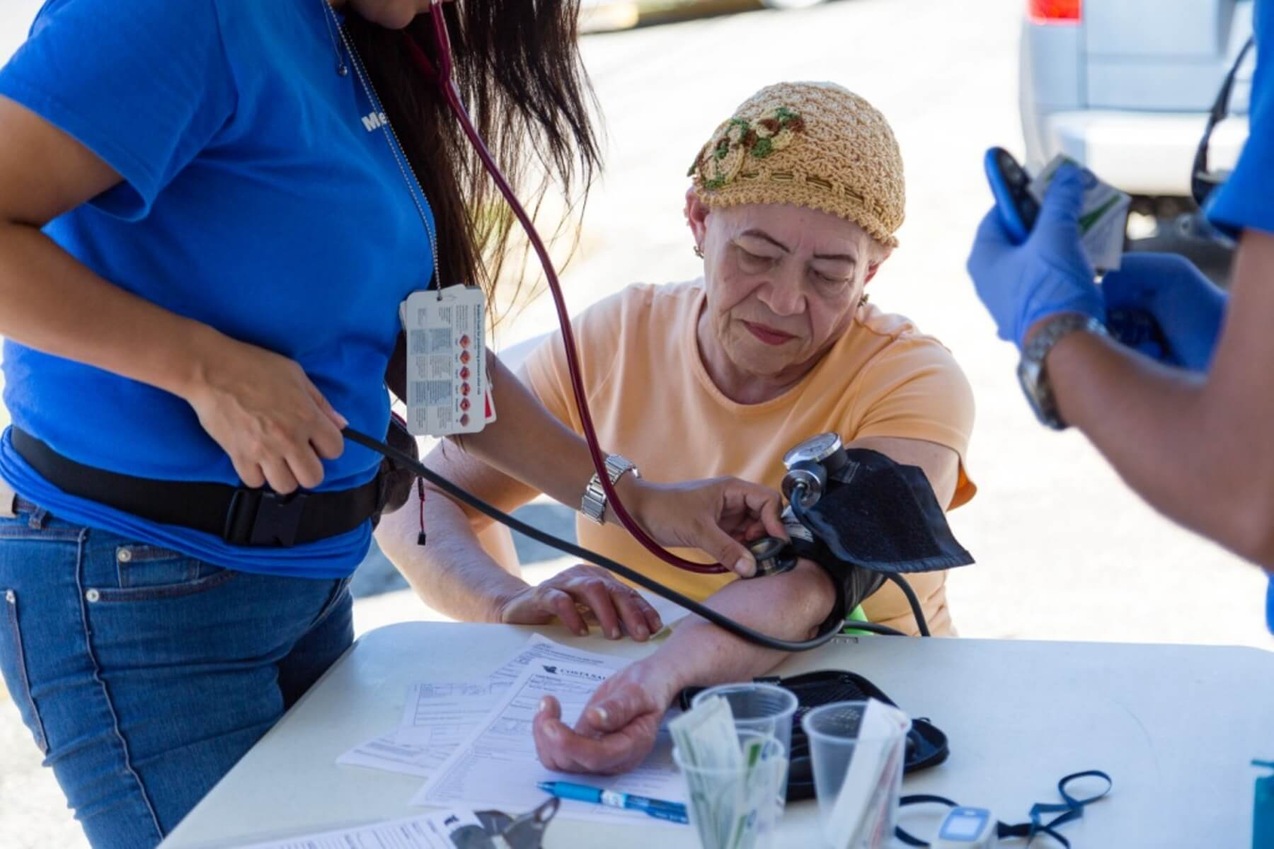 Relief worker takes blood pressure in an outdoor clinic in Puerto Rico