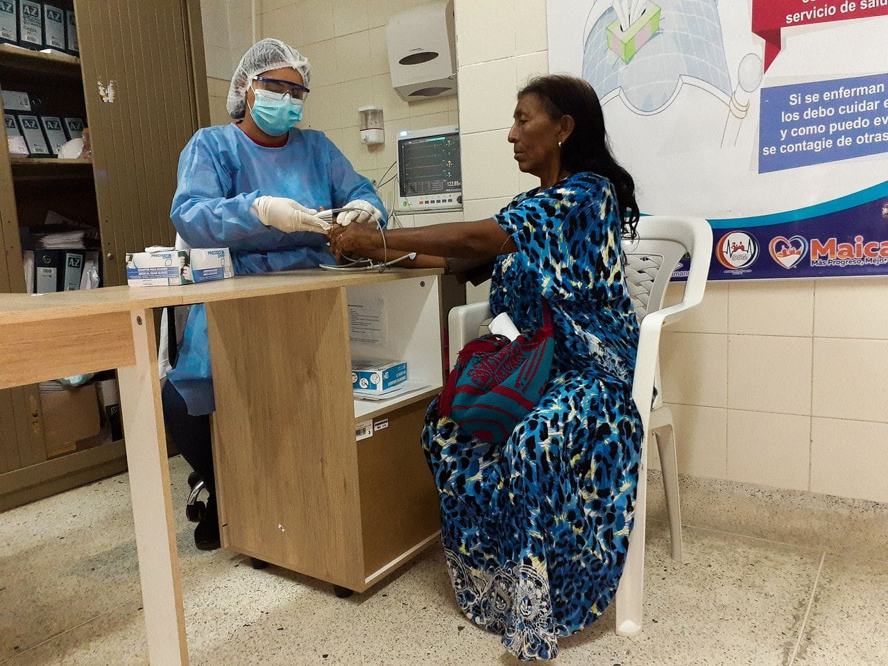 Nursing assistant taking blood pressure of patient at an Americares clinic in Colombia
