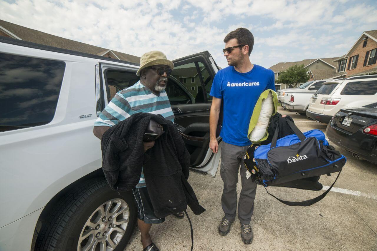 Americares worker helps a man out of an SUV