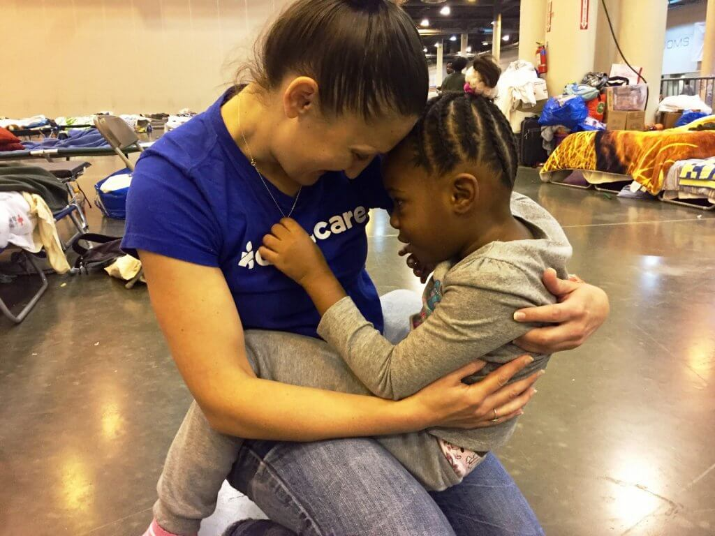 A young child plays with the necklace of an Americares worker as she holds her.