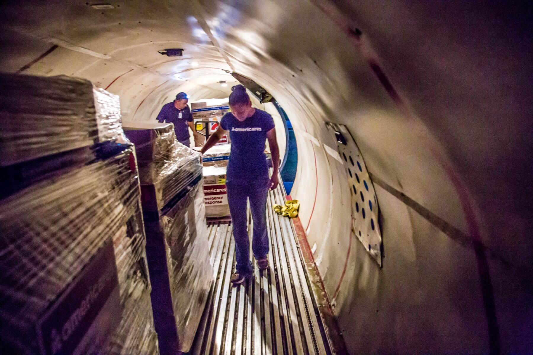 Photo of two Americares workers in the cargo hold of a plane with pallets of supplies.