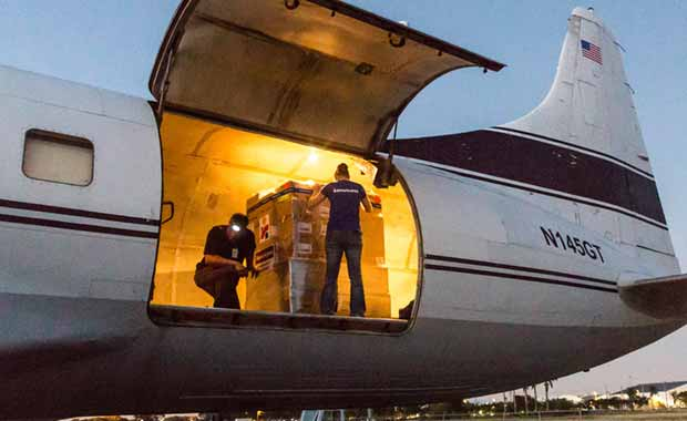 Photo of a cargo hold in a plane open and two Americares staff members readying a pallet of supplies for shipment.