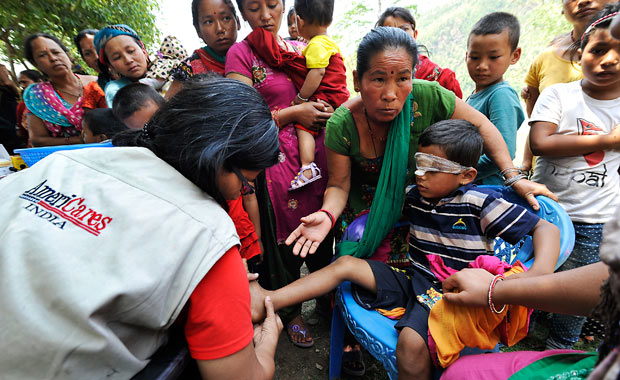 Dr. Swati Jha of AmeriCares India treats a 7-year-old earthquake survivor's infected wounds during a medical camp in Arughat, in Gorkha District.