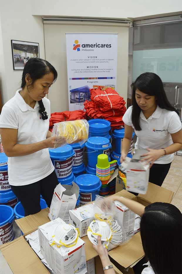 Americares relief workers pack protective masks to send to families staying in evacuation centers in Albay province.