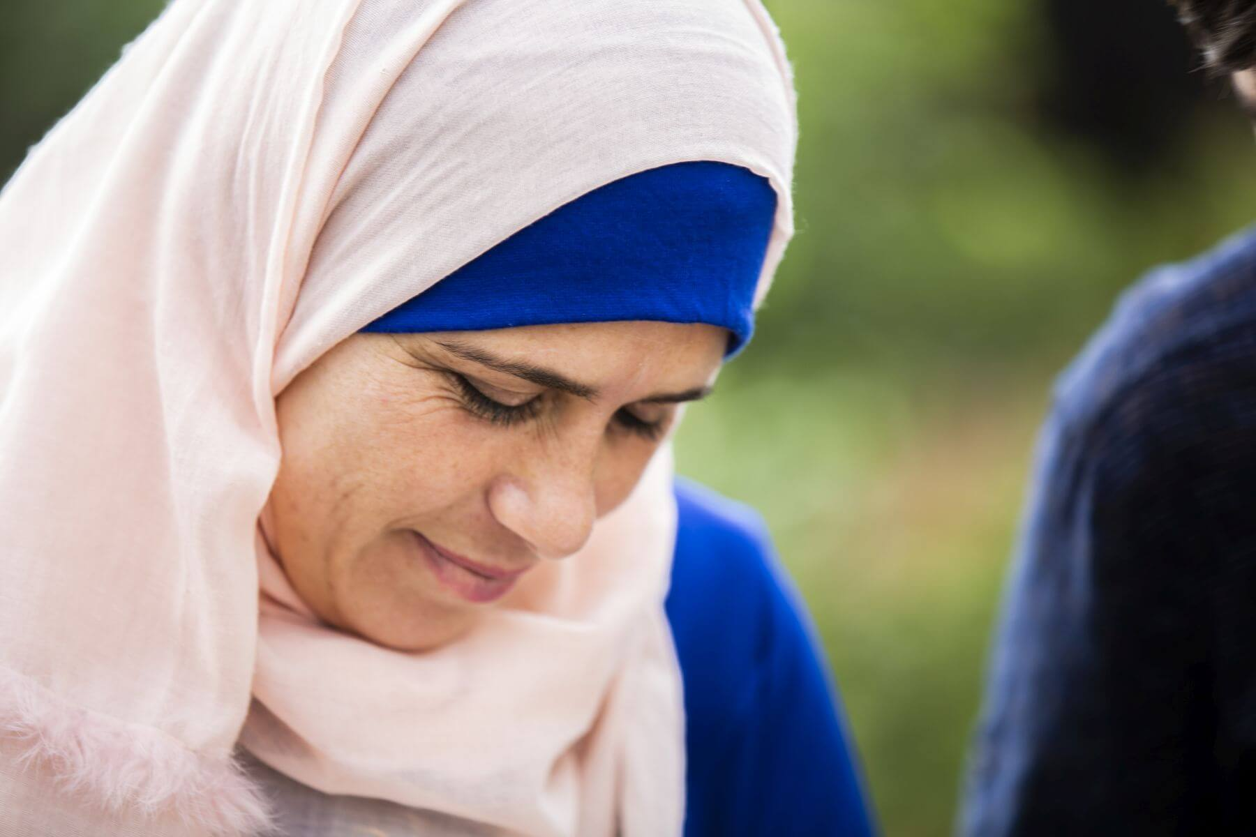 Close up photo of a woman in a headscarf looking down with a small smile.