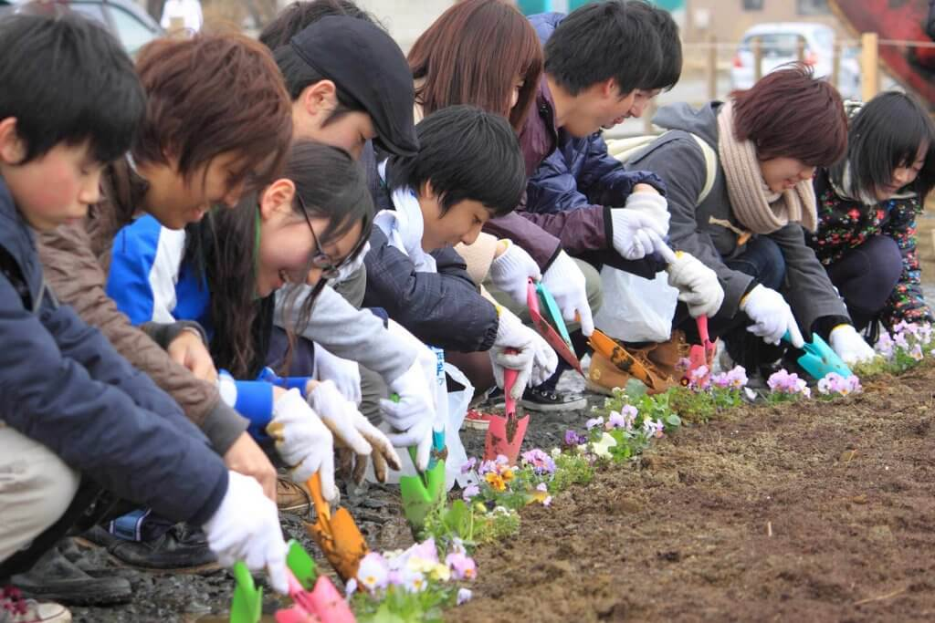 A line of young children plant flowers with plastic shovels and smiles.
