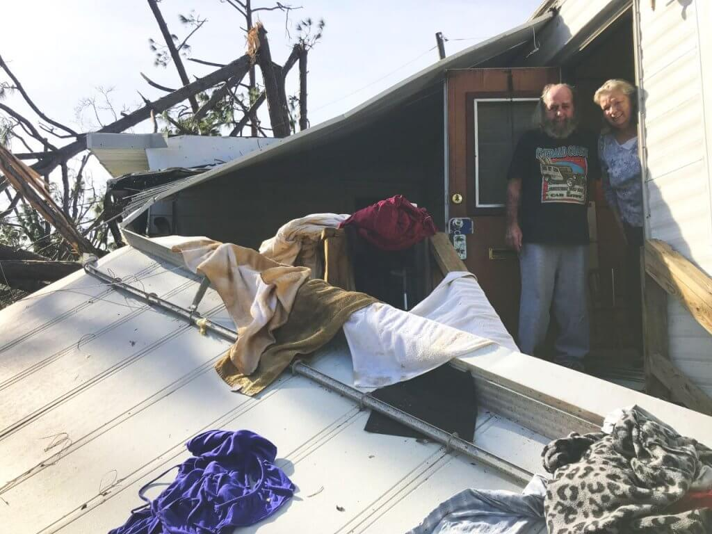 A husband and wife standing in their doorway of their damaged home with clothing and towels draping their staircase and fallen roof.